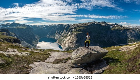 The girl stands on a large stone on top of a mountain near the trolltunga in Norway