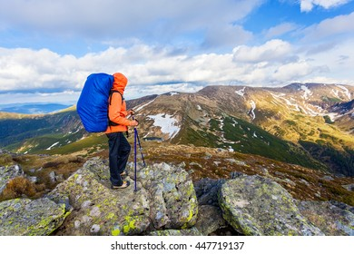 A girl stands on a mountain and looking into the distance