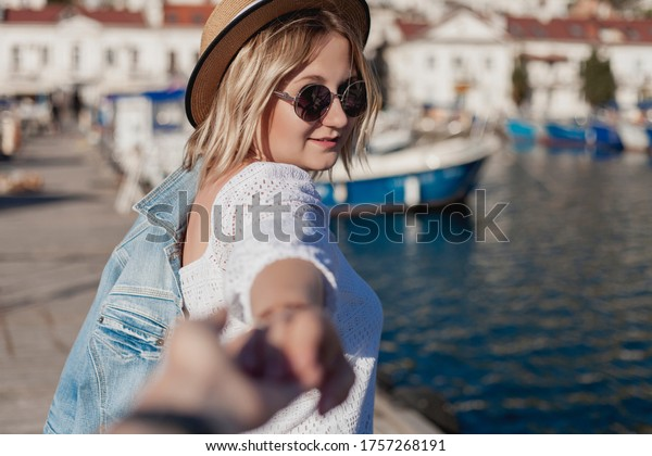 girl stands on the promenade near the sea. follow me - image