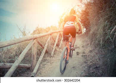 girl stands up to pedal along a steep climb. a ride to a woman in the hills in close contact with nature. Cyclist pedaling uphill with a backdrop of the sea at sunset.