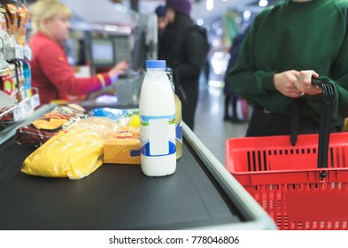 The girl stands at the supermarket and waits for a queue. The business makes purchases in the store.
