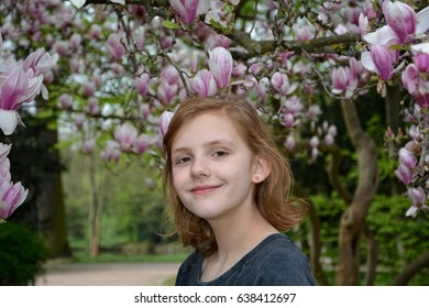 A Girl stands under blossoming magnolia trees   (  Magnoliaceae  )  and smiles forwards