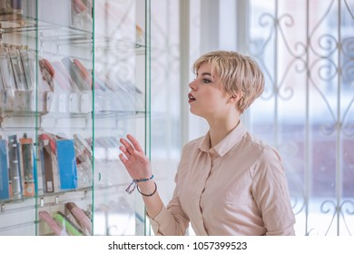 The girl stands at the window in the store