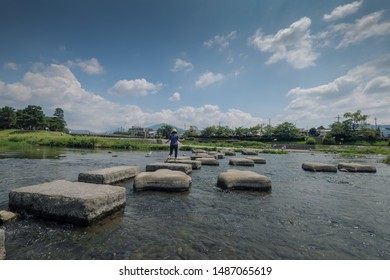 A girl Stepping stones crossing Kamogawa river.Kyoto, Japan.