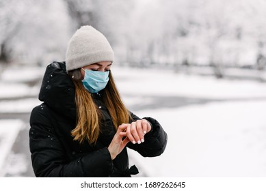 A girl in a sterile medical mask for viruses looks at the watch on her hand in a snowy spring day