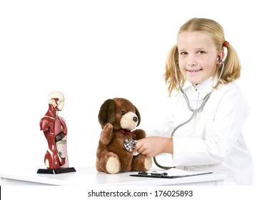 A girl with a stethoscope on the chest of a stuffed animal.