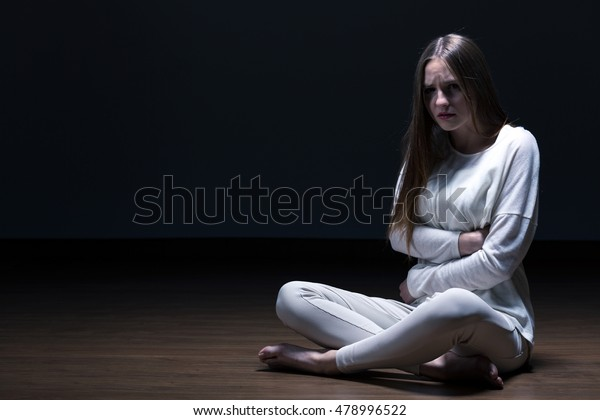 Girl with a stomachache sitting on the room floor