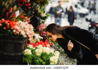 girl stopped to smell the flowers at a market in Paris France