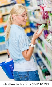 Girl at the store choosing cosmetics among the great variety of products. Concept of consumerism, retail and purchase