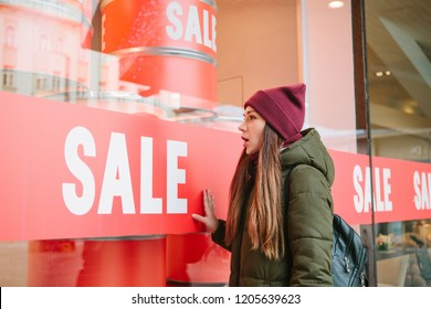 The girl at the storefront with a sale. She is surprised at low prices. Time of off-season and winter sales, Black Friday and Cyber Monday.