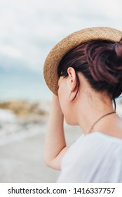 Girl with a straw hat by the sea