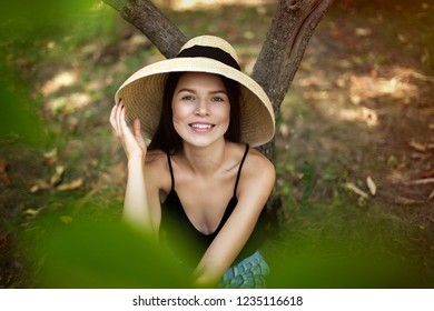 girl in a straw hat is resting on the nature under a tree. Large portrait. Healthy lifestyle