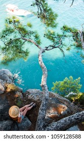 Girl in a straw hat sits on a rock under a tree. Woman looks at a boat in the sea. Top view of the pine branch on the rock. Tourist enjoys a beautiful view of the sea. Wild nature of Turkey, Kemer.