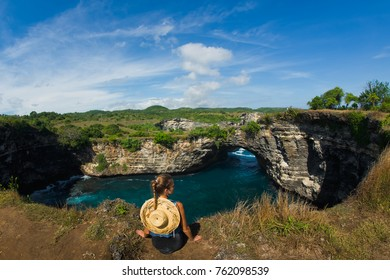 girl in a straw hat sits on a mountain