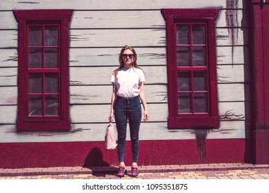 Girl street style urban hipster with a bag in a wood house background city scene