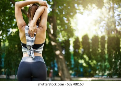 Girl stretching before a group yoga or pilates or fitness training standing outdoors in park or backyard. Morning excercise.