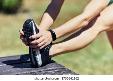 Girl stretching hamstrings with one leg over a wooden bench.