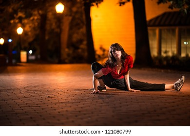 Girl stretching at night on brick floor in an urban street, wearing a red t-sh