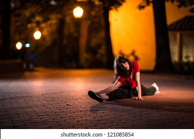 Girl stretching at night on brick floor in an urban street, wearing a red t-shirt
