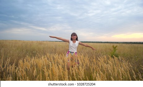 Girl stretching out her arms like wings and walking across field against blue sky smiling. Slow motion.