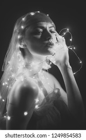 Girl with string with led lights around her body. Woman with mysterious face, black background. Lady in red outfit, coiled with led lights garland, holydays atmosphere. Led lights and garland concept.