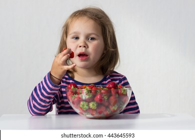 Girl in a striped dress eating strawberries from a glass plate at the table