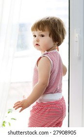 girl in striped dress standing at the window
