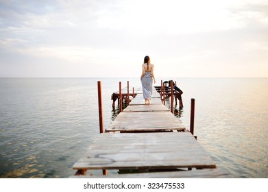 girl in a striped dress walking on a wooden bridge in the background of the sea