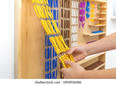 Girl in striped is playing and sorting a puzzle of colored plastic beads in montessori school. Concept of using a mathematical geometry learning resources children education.