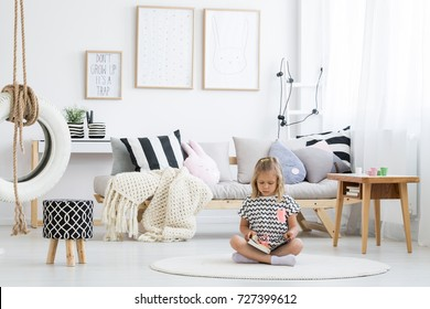 Girl in striped shirt reads book on white round carpet in kid room with tire on line