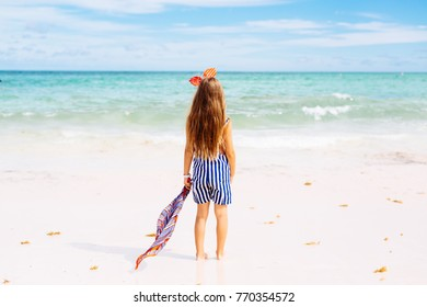Girl in striped shorts and red headband standing infront of ocean waves