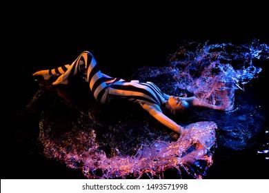 Girl in stripped body lying in water in the dark