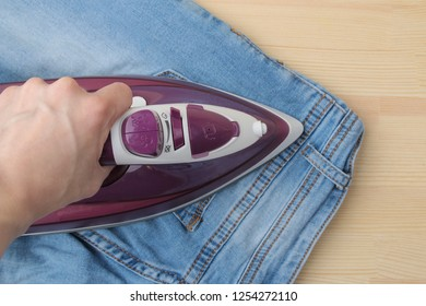 Girl strokes jeans. lilac iron and jeans. ironing clothes household electrical appliances. view from above