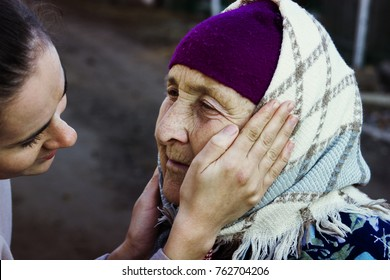 The girl is stroking the face of her old grandmother
