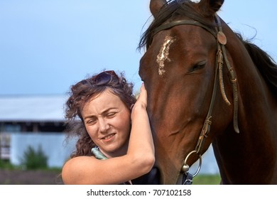 Girl  stroking the head of a horse. Sunny day on the farm. In the background a green meadow
