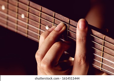 Girl strumming the strings of a guitar.