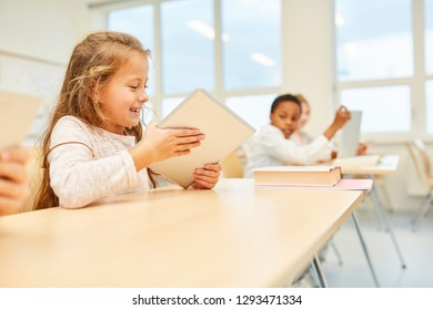 Girl as a student in elementary school lessons is having fun learning
