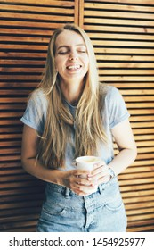 Girl student hipster blonde with long hair laughs from a fun joke. Paper cup with coffee in hand. Youth coffee break for happy moments.