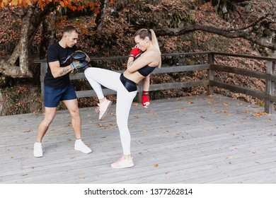 Girl student and a male martial arts coach are engaged in kickboxing in protective gear in the open air. Concept of sports and stamina