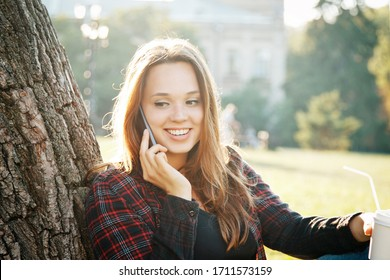 girl student near a tree is waiting for the start of the lesson and dreams