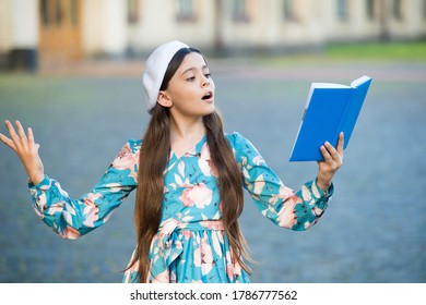 Girl student reading book outdoors, recite poetry concept.