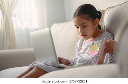 girl student  sitting at the table, writing homework . Teen using laptop computer to study.New normal.Social distancing stay home
