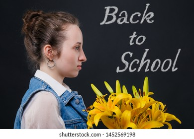 Girl student is waiting for the teacher with flowers in their hands. Behind her on blackboard text: Back to school