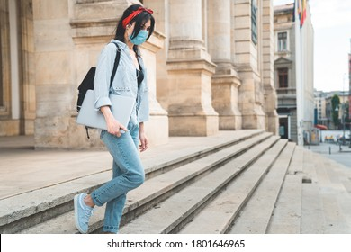 Girl student wearing protective face mask walking down university stairs during pandemic
