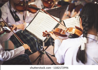 girl students playing violin in the group.