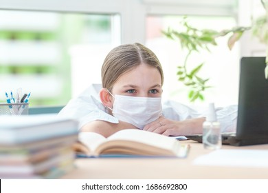 The girl studies at home in a protective face mask during Quarantine CoVid-19. She is tired of studying at home. Distance learning online with a laptop. The child is doing homework for school. The sch