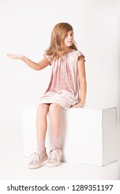 A girl in the studio sits and holds an imaginary object on the palm.