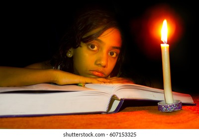 girl studying  in candle light- no electricity, blackout