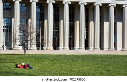 Girl studying in front of university building