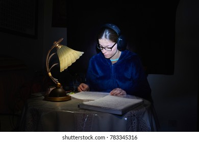 girl studying illuminated by a lamp